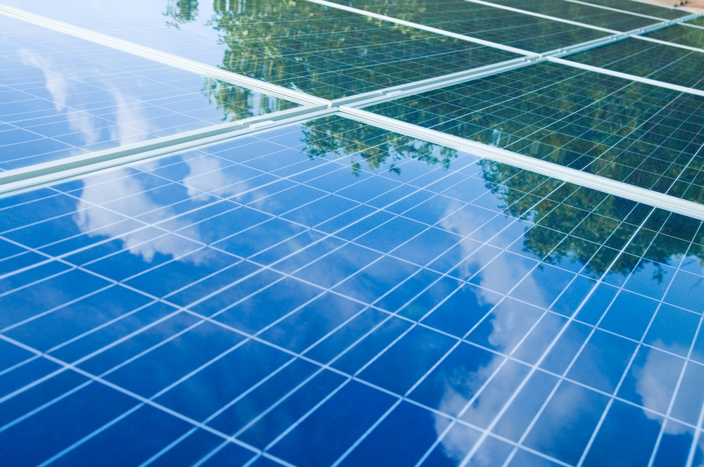 Solar panels reflecting sky and trees