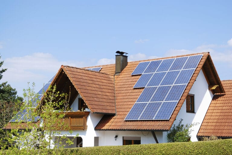 Tiled roof with solar panels, blue sky